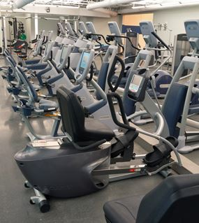 Row of exercise equipment including stationary bikes and ellipticals