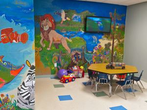 Child Care room featuring mural painted walls and a small seating area