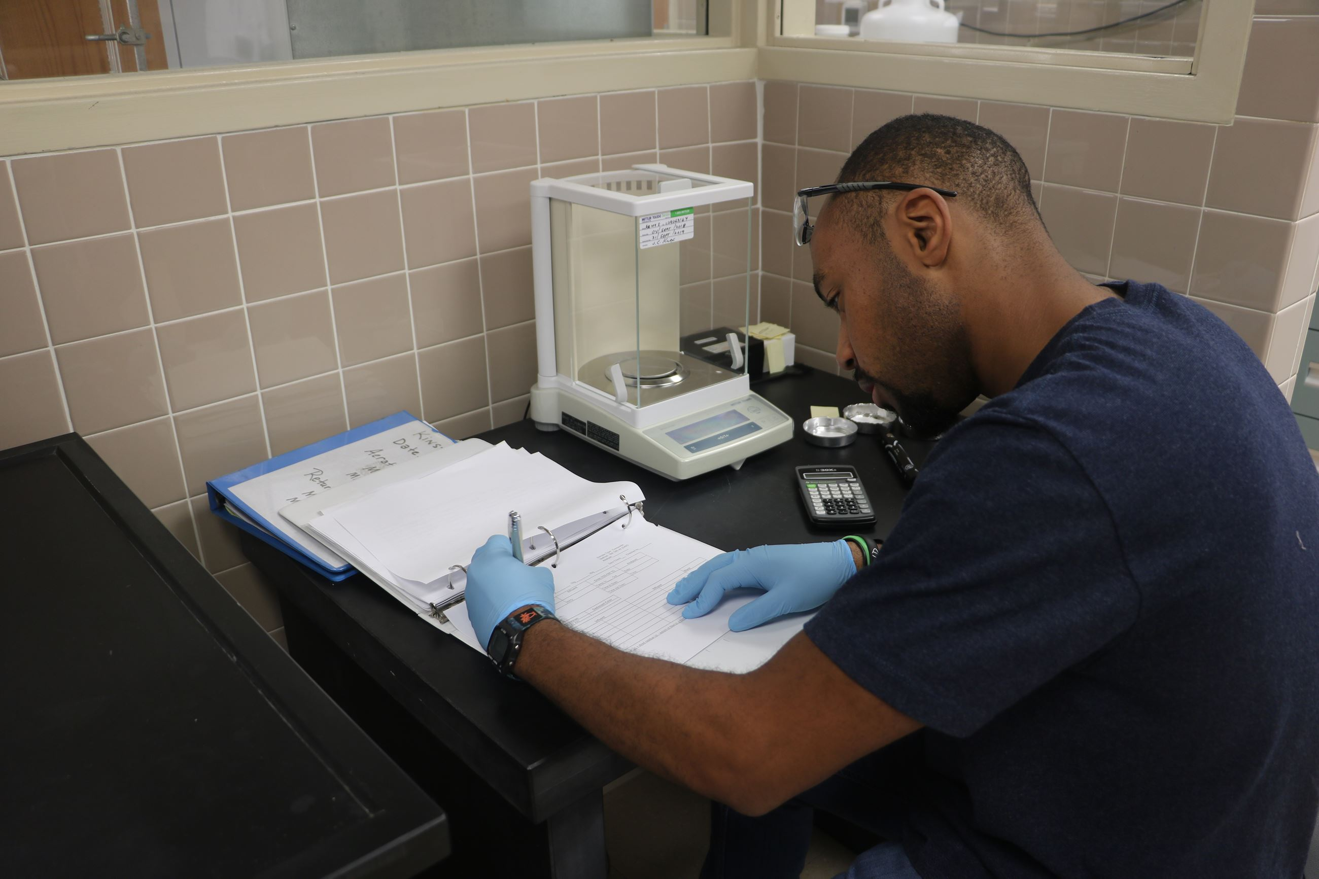An intern records data in the lab