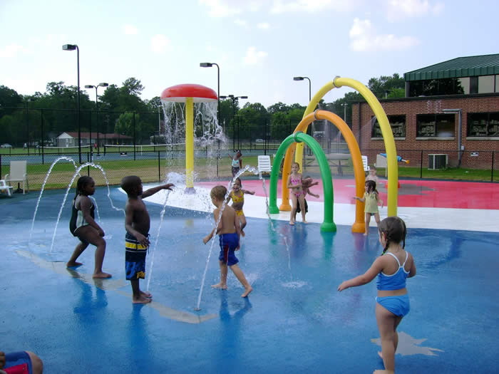Children playing in the splash pad water features