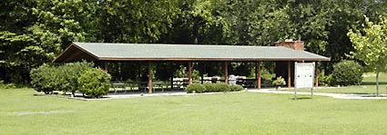 A large picnic shelter in front of trees.
