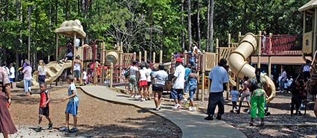 A playground with a large amount of kids playing on it.
